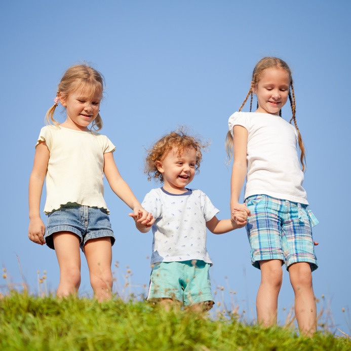 two little girls and little boy standing on the road