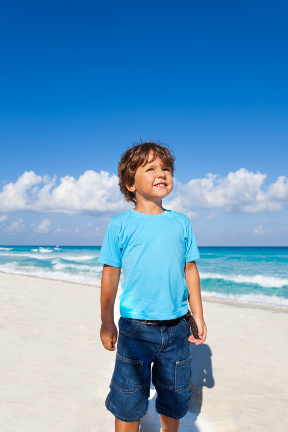 Cute kid standing on the sandy beach of the seashore during summer day